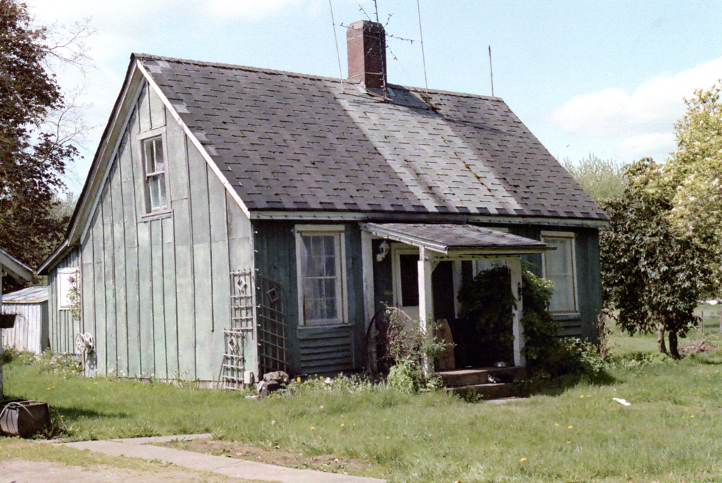 Small faded green house with a gabled roof running horizontal with a small sheltered entrance and two front windows.